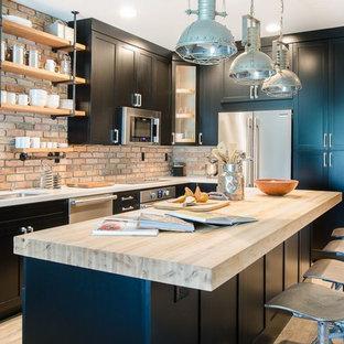 マイアミの小さいインダストリアルスタイルのおしゃれなアイランドキッチン (ダブルシンク、シェーカースタイル扉のキャビネット、黒いキャビネット、クオーツストーンカウンター、テラコッタタイルのキッチンパネル、シルバーの調理設備の、クッションフロア) の写真