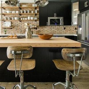 マイアミの小さいインダストリアルスタイルのおしゃれなアイランドキッチン (ダブルシンク、シェーカースタイル扉のキャビネット、黒いキャビネット、クオーツストーンカウンター、テラコッタタイルのキッチンパネル、シルバーの調理設備、クッションフロア) の写真