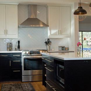 ローリーの中サイズのインダストリアルスタイルのおしゃれなキッチン (アンダーカウンターシンク、シェーカースタイル扉のキャビネット、黒いキャビネット、クオーツストーンカウンター、白いキッチンパネル、セラミックタイルのキッチンパネル、シルバーの調理設備の、無垢フローリング、茶色い床、白いキッチンカウンター) の写真