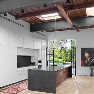 他の地域の広いインダストリアルスタイルのおしゃれなキッチン (アンダーカウンターシンク、フラットパネル扉のキャビネット、白いキャビネット、ライムストーンカウンター、黒いキッチンパネル、パネルと同色の調理設備、淡色無垢フローリング、茶色い床) の写真
