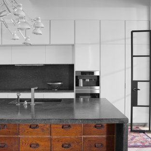 Große, Offene, Einzeilige Industrial Küche mit Unterbauwaschbecken, flächenbündigen Schrankfronten, weißen Schränken, hellem Holzboden, Kücheninsel, Kalkstein-Arbeitsplatte, Küchenrückwand in Schwarz und Elektrogeräten mit Frontblende in Sonstige