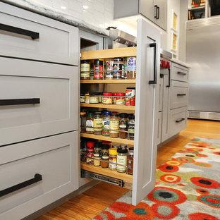 セントルイスの小さいインダストリアルスタイルのおしゃれなキッチン (アンダーカウンターシンク、シェーカースタイル扉のキャビネット、グレーのキャビネット、大理石カウンター、白いキッチンパネル、セラミックタイルのキッチンパネル、シルバーの調理設備の、淡色無垢フローリング、茶色い床、白いキッチンカウンター) の写真
