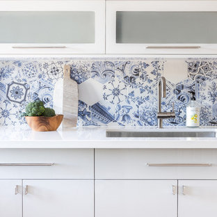 This is an example of a mid-sized modern l-shaped eat-in kitchen in Toronto with an undermount sink, flat-panel cabinets, white cabinets, quartz benchtops, blue splashback, porcelain splashback, stainless steel appliances, medium hardwood floors, no island and grey floor.