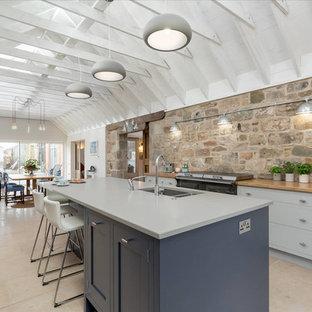 Пример оригинального дизайна: большая кухня в стиле кантри с обеденным столом, плоскими фасадами, серыми фасадами, столешницей из кварцита, техникой из нержавеющей стали, полом из травертина, островом и врезной раковиной