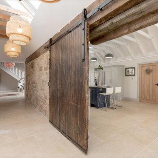 Inredning av ett industriellt stort kök och matrum, med släta luckor, grå skåp, rostfria vitvaror, travertin golv, en köksö, en undermonterad diskho och beiget golv