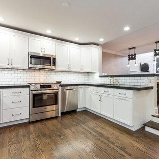 シカゴの中サイズのインダストリアルスタイルのおしゃれなキッチン (アンダーカウンターシンク、シェーカースタイル扉のキャビネット、白いキャビネット、クオーツストーンカウンター、白いキッチンパネル、サブウェイタイルのキッチンパネル、シルバーの調理設備の、濃色無垢フローリング、アイランドなし、茶色い床) の写真