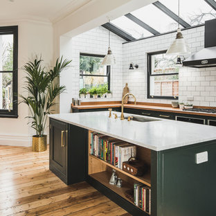 Large urban galley kitchen/diner in London with a submerged sink, shaker cabinets, green cabinets, wood worktops, white splashback, metro tiled splashback, cement flooring, an island and grey floors.