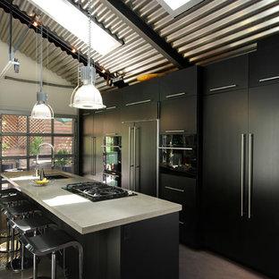 Immagine di una cucina parallela industriale con top in cemento, lavello a vasca singola, ante lisce, ante nere e elettrodomestici da incasso