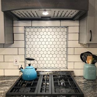 デンバーの大きいインダストリアルスタイルのおしゃれなキッチン (シングルシンク、シェーカースタイル扉のキャビネット、濃色木目調キャビネット、御影石カウンター、白いキッチンパネル、セラミックタイルのキッチンパネル、シルバーの調理設備、淡色無垢フローリング、茶色い床、グレーのキッチンカウンター) の写真