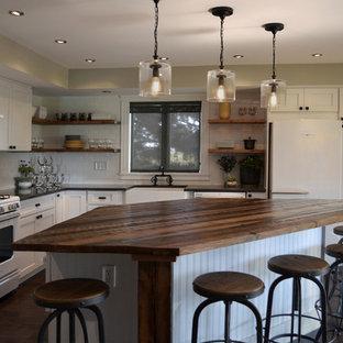 シカゴの大きいインダストリアルスタイルのおしゃれなキッチン (エプロンフロントシンク、シェーカースタイル扉のキャビネット、白いキャビネット、木材カウンター、白いキッチンパネル、サブウェイタイルのキッチンパネル、白い調理設備、無垢フローリング、茶色い床) の写真
