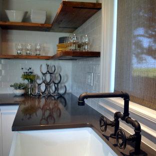 シカゴのインダストリアルスタイルのおしゃれなキッチン (エプロンフロントシンク、シェーカースタイル扉のキャビネット、白いキャビネット、クオーツストーンカウンター、白いキッチンパネル、サブウェイタイルのキッチンパネル、無垢フローリング) の写真