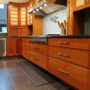 Photo of a mid-sized industrial u-shaped separate kitchen in New York with an undermount sink, flat-panel cabinets, medium wood cabinets, granite benchtops, blue splashback, glass tile splashback, stainless steel appliances, porcelain floors, with island and grey floor.
