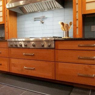 ニューヨークの中くらいのインダストリアルスタイルのおしゃれなキッチン (アンダーカウンターシンク、フラットパネル扉のキャビネット、中間色木目調キャビネット、御影石カウンター、青いキッチンパネル、ガラスタイルのキッチンパネル、シルバーの調理設備、磁器タイルの床、グレーの床) の写真