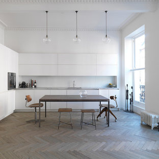 Photo of a scandi l-shaped kitchen/diner in London with a submerged sink, flat-panel cabinets, white cabinets, light hardwood flooring and no island.