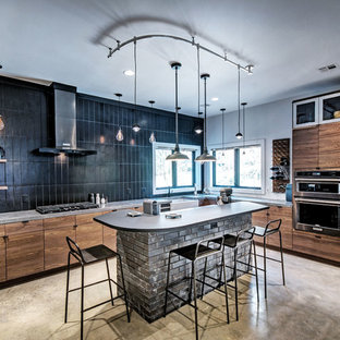 Industrial kitchen inspiration - Example of an urban l-shaped gray floor kitchen design in Jackson with a farmhouse sink, flat-panel cabinets, brown cabinets, black backsplash, subway tile backsplash, an island and gray countertops