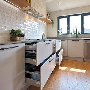 Foto på ett mellanstort industriellt grå kök, med en nedsänkt diskho, släta luckor, grå skåp, bänkskiva i kvartsit, vitt stänkskydd, stänkskydd i keramik, rostfria vitvaror, laminatgolv, en köksö och brunt golv