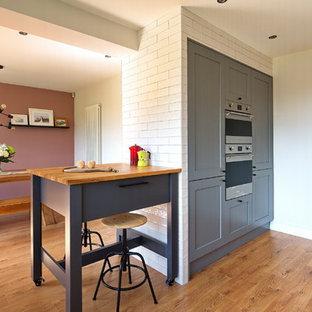 他の地域の中サイズのインダストリアルスタイルのおしゃれなキッチン (ドロップインシンク、フラットパネル扉のキャビネット、グレーのキャビネット、珪岩カウンター、白いキッチンパネル、セラミックタイルのキッチンパネル、シルバーの調理設備の、ラミネートの床、茶色い床、グレーのキッチンカウンター) の写真
