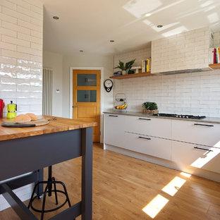 Idéer för mellanstora industriella grått kök, med en nedsänkt diskho, släta luckor, grå skåp, bänkskiva i kvartsit, vitt stänkskydd, stänkskydd i keramik, rostfria vitvaror, laminatgolv, en köksö och brunt golv
