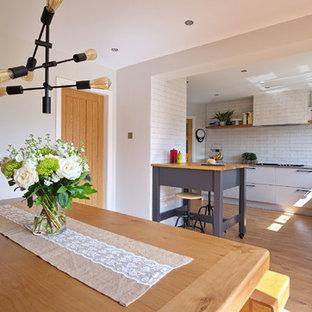 ベルファストの中サイズのインダストリアルスタイルのおしゃれなキッチン (ドロップインシンク、フラットパネル扉のキャビネット、グレーのキャビネット、珪岩カウンター、白いキッチンパネル、セラミックタイルのキッチンパネル、シルバーの調理設備の、ラミネートの床、茶色い床、グレーのキッチンカウンター) の写真