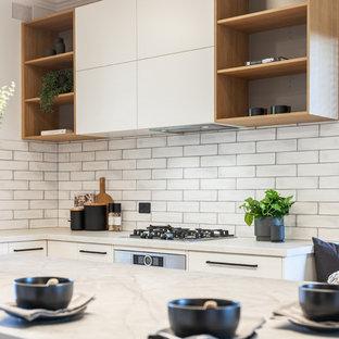 Bild på ett stort funkis grå grått kök, med en dubbel diskho, släta luckor, vita skåp, bänkskiva i kvarts, vitt stänkskydd, stänkskydd i tunnelbanekakel, svarta vitvaror, ljust trägolv, en köksö och gult golv