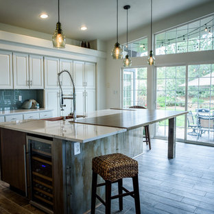 Large industrial l-shaped open plan kitchen in Denver with a farmhouse sink, raised-panel cabinets, white cabinets, quartz benchtops, blue splashback, glass tile splashback, stainless steel appliances, porcelain floors and with island.