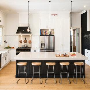 Bild på ett stort vintage kök, med ljust trägolv, en köksö, en dubbel diskho, luckor med infälld panel, svarta skåp, bänkskiva i kvarts, vitt stänkskydd, stänkskydd i tunnelbanekakel och rostfria vitvaror