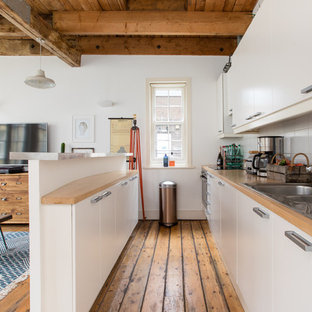 Industrial single-wall kitchen in London with a built-in sink, flat-panel cabinets, white cabinets, wood worktops, white splashback, medium hardwood flooring, an island and brown floors.
