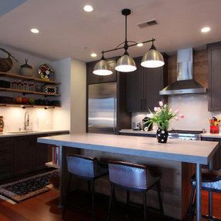 他の地域の中くらいのインダストリアルスタイルのおしゃれなキッチン (フラットパネル扉のキャビネット、淡色木目調キャビネット、コンクリートカウンター、シルバーの調理設備、濃色無垢フローリング、赤い床、グレーのキッチンカウンター) の写真
