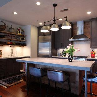 Mittelgroße Industrial Küche in L-Form mit flächenbündigen Schrankfronten, hellen Holzschränken, Betonarbeitsplatte, Küchengeräten aus Edelstahl, dunklem Holzboden, Kücheninsel, rotem Boden und grauer Arbeitsplatte in Sonstige