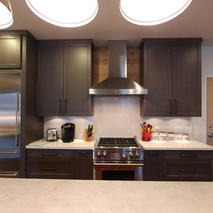Photo of a mid-sized industrial l-shaped kitchen in Other with flat-panel cabinets, light wood cabinets, concrete benchtops, stainless steel appliances, dark hardwood floors, with island, red floor, grey benchtop and an undermount sink.
