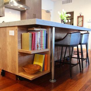 Idee per una cucina a L industriale di medie dimensioni con ante lisce, ante in legno chiaro, top in cemento, elettrodomestici in acciaio inossidabile, parquet scuro, isola, pavimento rosso e top grigio