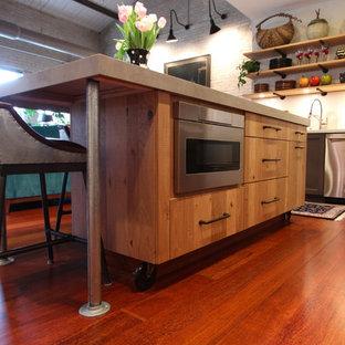 他の地域の小さいインダストリアルスタイルのおしゃれなキッチン (フラットパネル扉のキャビネット、淡色木目調キャビネット、コンクリートカウンター、シルバーの調理設備の、濃色無垢フローリング、赤い床、グレーのキッチンカウンター) の写真