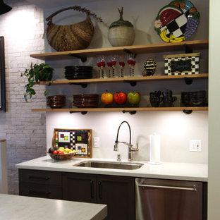 他の地域の中サイズのインダストリアルスタイルのおしゃれなキッチン (フラットパネル扉のキャビネット、淡色木目調キャビネット、コンクリートカウンター、シルバーの調理設備の、濃色無垢フローリング、赤い床、グレーのキッチンカウンター、アンダーカウンターシンク) の写真