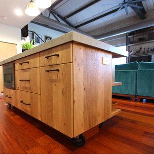 他の地域のインダストリアルスタイルのおしゃれなアイランドキッチン (フラットパネル扉のキャビネット、淡色木目調キャビネット、コンクリートカウンター、シルバーの調理設備、濃色無垢フローリング、赤い床、グレーのキッチンカウンター) の写真