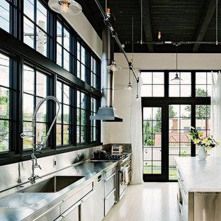 Foto på ett stort industriellt vit linjärt kök och matrum, med en integrerad diskho, släta luckor, skåp i rostfritt stål, bänkskiva i rostfritt stål, vitt stänkskydd, rostfria vitvaror, ljust trägolv, en köksö och brunt golv