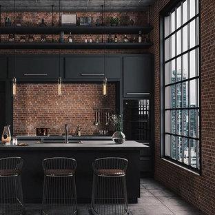 Idées déco pour une cuisine américaine linéaire industrielle de taille moyenne avec un évier posé, un placard à porte plane, des portes de placard noires, un plan de travail en béton, une crédence marron, une crédence en brique, un électroménager en acier inoxydable, béton au sol, un îlot central, un sol gris et un plan de travail gris.