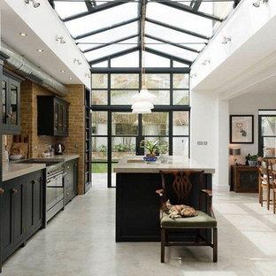 Idéer för ett stort industriellt grå linjärt kök och matrum, med en undermonterad diskho, luckor med infälld panel, svarta skåp, bänkskiva i betong, brunt stänkskydd, stänkskydd i tegel, rostfria vitvaror, betonggolv, en köksö och grått golv