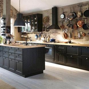 Exempel på ett mellanstort industriellt brun linjärt brunt kök och matrum, med en nedsänkt diskho, luckor med infälld panel, svarta skåp, träbänkskiva, brunt stänkskydd, stänkskydd i tegel, svarta vitvaror, mellanmörkt trägolv, en köksö och grått golv