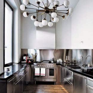 コロンバスの中サイズのインダストリアルスタイルのおしゃれなキッチン (アンダーカウンターシンク、フラットパネル扉のキャビネット、ステンレスキャビネット、御影石カウンター、メタリックのキッチンパネル、シルバーの調理設備の、無垢フローリング、茶色い床、黒いキッチンカウンター) の写真