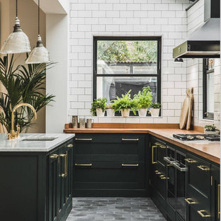 Inspiration for a mid-sized industrial l-shaped eat-in kitchen in Columbus with an undermount sink, recessed-panel cabinets, black cabinets, wood benchtops, brown splashback, timber splashback, black appliances, marble floors, with island, grey floor and brown benchtop.