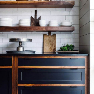 Design ideas for a mid-sized industrial single-wall eat-in kitchen in Columbus with an undermount sink, recessed-panel cabinets, black cabinets, quartz benchtops, white splashback, subway tile splashback, stainless steel appliances, dark hardwood floors, with island, black floor and black benchtop.