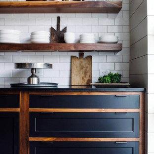 コロンバスの中サイズのインダストリアルスタイルのおしゃれなキッチン (アンダーカウンターシンク、落し込みパネル扉のキャビネット、黒いキャビネット、クオーツストーンカウンター、白いキッチンパネル、サブウェイタイルのキッチンパネル、シルバーの調理設備の、濃色無垢フローリング、黒い床、黒いキッチンカウンター) の写真
