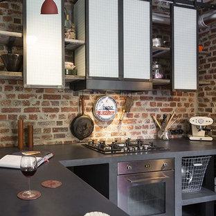 Esempio di una piccola cucina industriale con lavello da incasso, nessun'anta, ante nere, top in cemento, paraspruzzi marrone, paraspruzzi in mattoni, elettrodomestici neri, pavimento in cemento, penisola, pavimento grigio e top nero