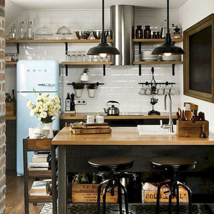 Inspiration for a small industrial l-shaped medium tone wood floor and brown floor eat-in kitchen remodel in Columbus with a drop-in sink, recessed-panel cabinets, black cabinets, wood countertops, white backsplash, ceramic backsplash, colored appliances, an island and brown countertops