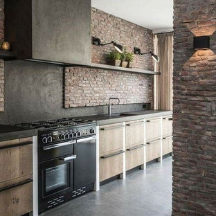 Eat-in kitchen - mid-sized industrial single-wall concrete floor and gray floor eat-in kitchen idea in Columbus with an undermount sink, flat-panel cabinets, light wood cabinets, granite countertops, black backsplash, brick backsplash, black appliances, an island and black countertops