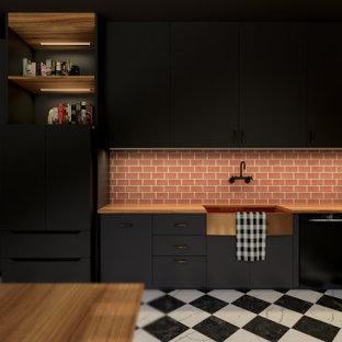 Inspiration för mellanstora industriella svart kök, med en undermonterad diskho, släta luckor, svarta skåp, träbänkskiva, svarta vitvaror, klinkergolv i keramik, en köksö och svart golv