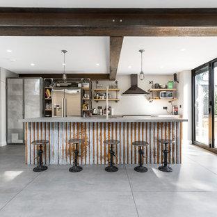 ロンドンの広いインダストリアルスタイルのおしゃれなキッチン (一体型シンク、フラットパネル扉のキャビネット、中間色木目調キャビネット、コンクリートカウンター、レンガのキッチンパネル、シルバーの調理設備、コンクリートの床、グレーの床) の写真