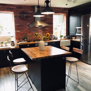 Inspiration för stora industriella brunt kök, med en rustik diskho, luckor med upphöjd panel, svarta skåp, träbänkskiva, svarta vitvaror, mörkt trägolv, en köksö och flerfärgat golv