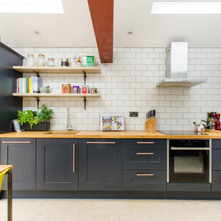 Medium sized classic single-wall kitchen/diner in Kent with blue cabinets, wood worktops, white splashback, metro tiled splashback, beige floors, a submerged sink, integrated appliances and recessed-panel cabinets.