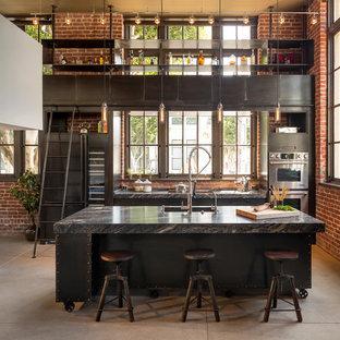 Foto di una cucina industriale con ante lisce, elettrodomestici in acciaio inossidabile, pavimento in cemento e isola